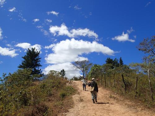 農機具を担ぐ村人と青い空