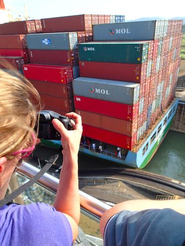 貨物船を撮影する女性