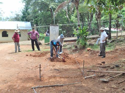 硬い地面をツルハシで掘る