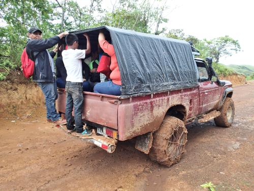 車の荷台に捕まる人