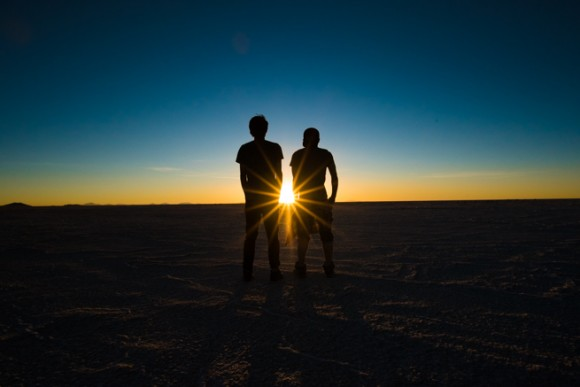 ウユニ塩湖の夕陽を眺める二人組