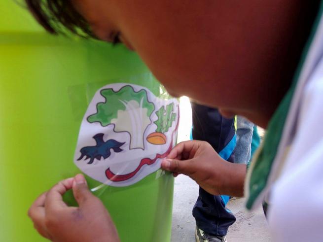 ウユニの学校でごみ箱に絵を貼る学生