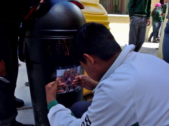 ウユニ市の学校でごみ箱に絵を貼る生徒