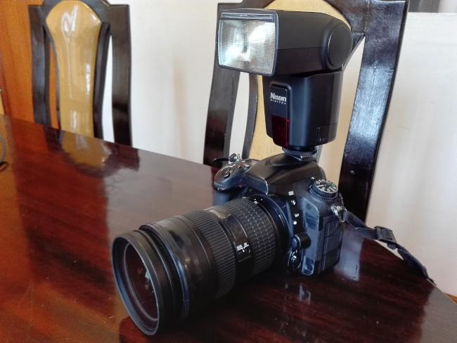 ストロボをつけた一眼レフカメラ