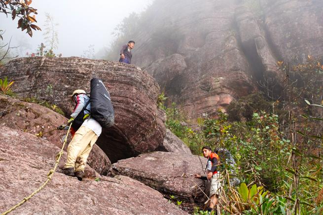 アウヤンテプイでロープを使って岩を登る私