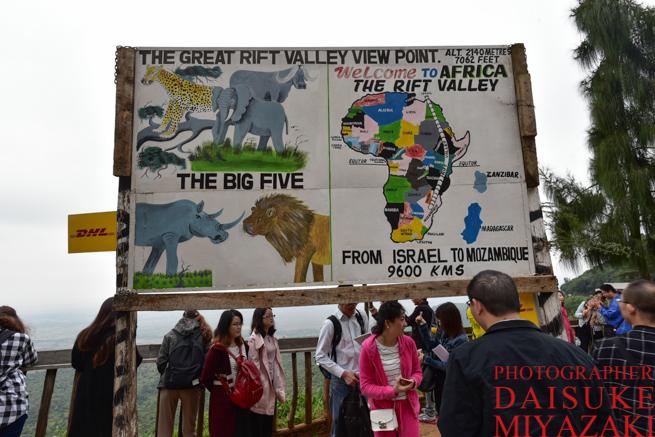 ケニアのグレート・リフト・バレーの看板と観光客