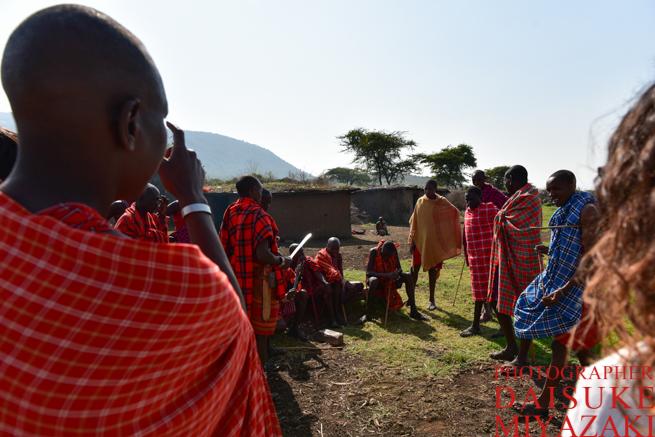 マサイ族で長老から説明を受ける観光客