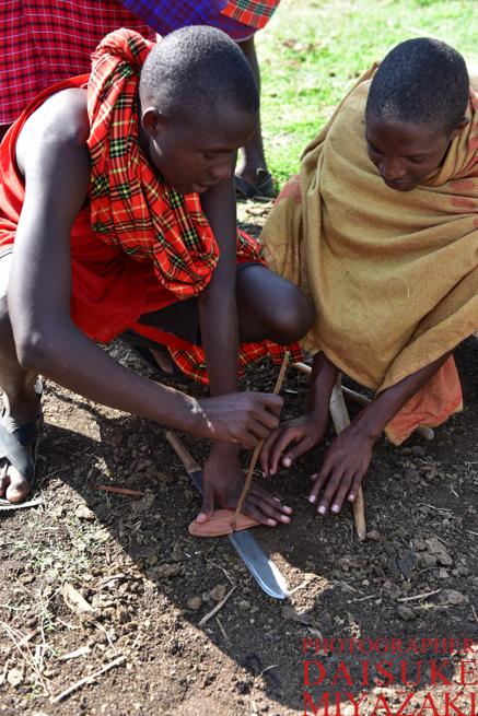 木の棒で火をつけようとするマサイ族