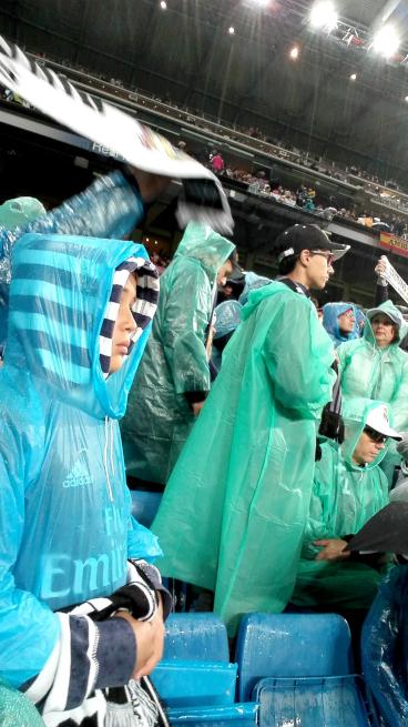 雨合羽を着るサポーター